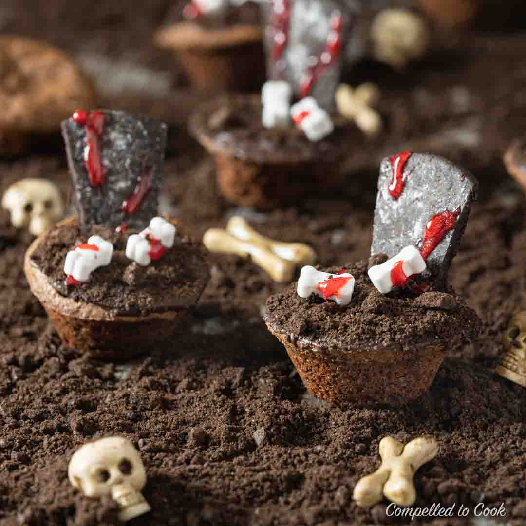 Graveyard Brownie Bites resting on crumbled cookie dirt scattered with sculls and bones.