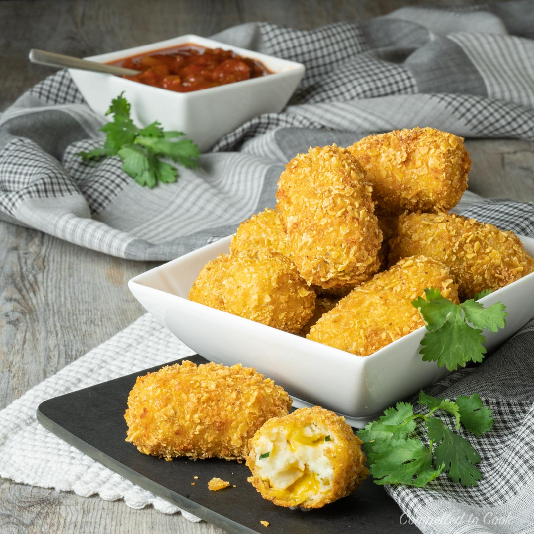 Mexican Jalapeno Cheddar Croquettes piled high in while bowl and garnished with fresh cilantro.
