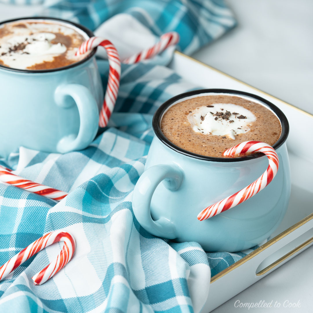 Minty Hot Chocolate with whipped cream in blue mugs resting on a white tray lined with a checkered blue and white napkin.
