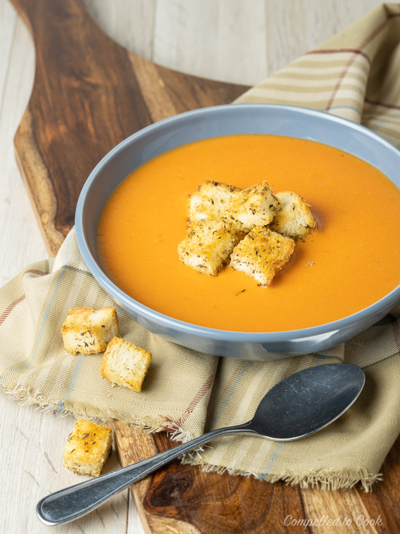 Tomato Bisque with crutons served in a shallow blue bowl resting on a wooden board draped with a striped napkin.