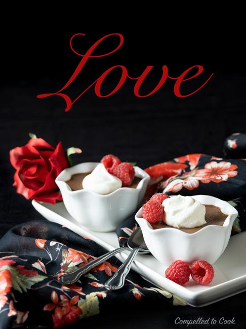 Chocolate Pots de Creme in small white ramekins, garnished fresh raspberries and whipped cream.