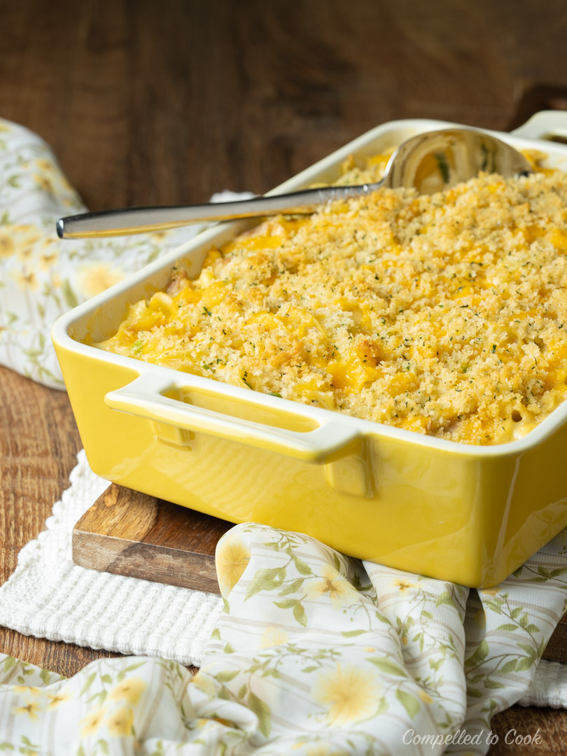 Baked golden Tuna Noodle Casserole in a yellow serving dish on a wooden trivet.