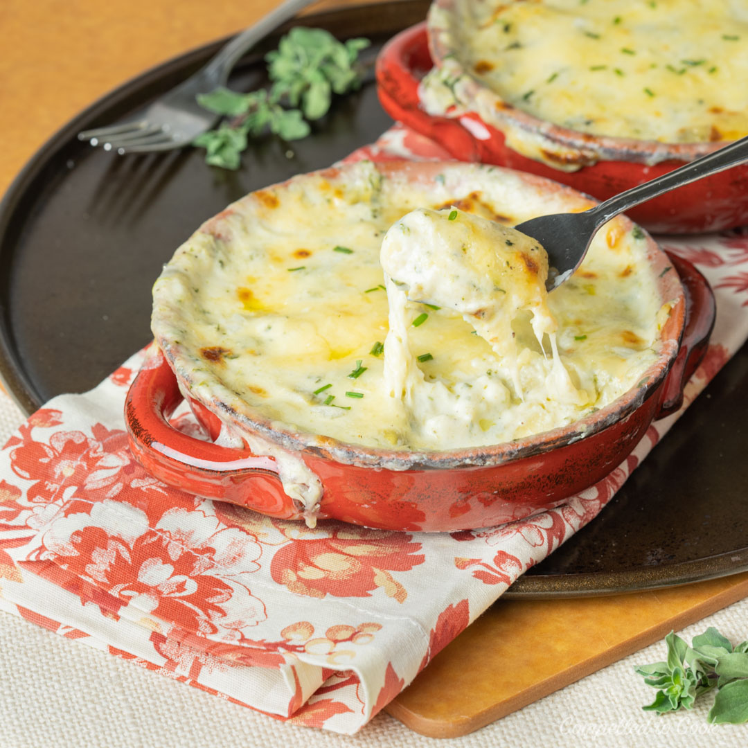 Spinach and Artichoke Gnocchi Gratin baked in small red ceramic cocotte dishes.