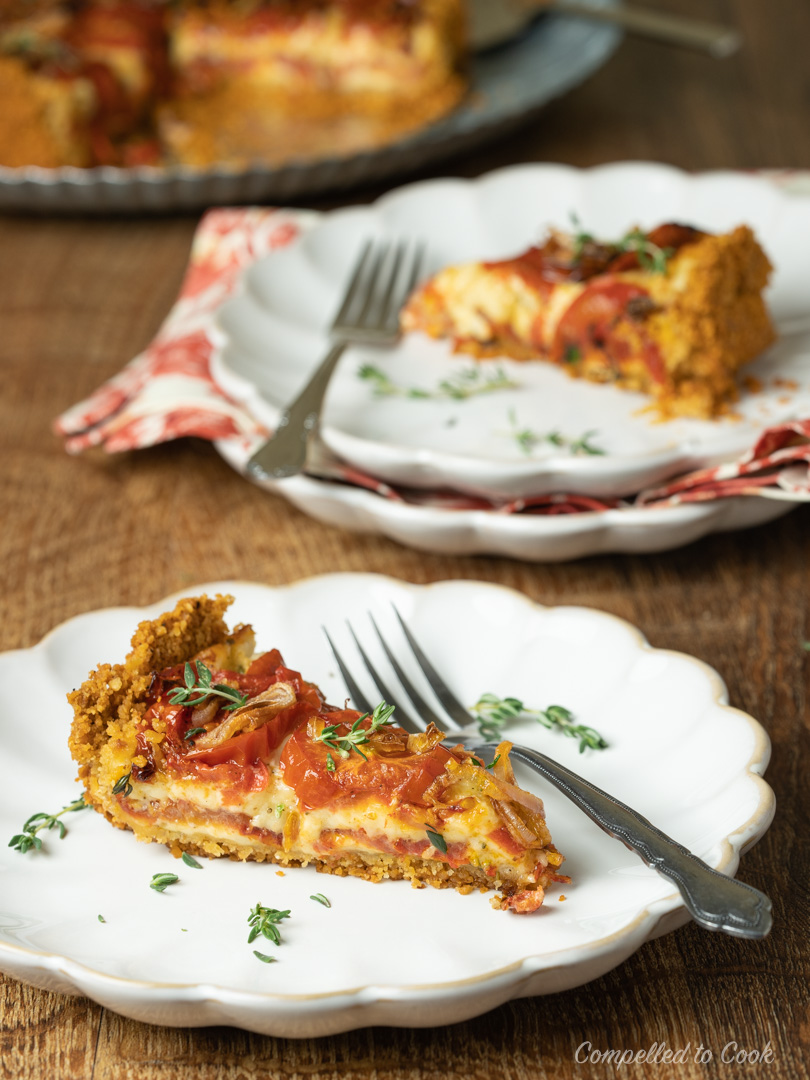 A slice of Tomato and Roasted Garlic Pie on a serving plate garnished with fresh thyme leaves.