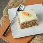 A piece of Super Moist Carrot Cake on a small white plate resting on an orange napkin.