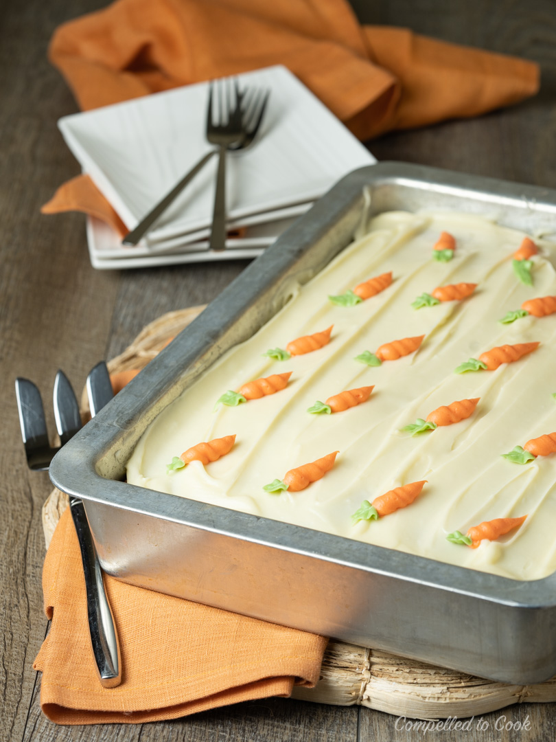 """Super Moist Carrot Cake in a 9""""x13"""" pan with cream cheese icing and decorated with piped carrots."""
