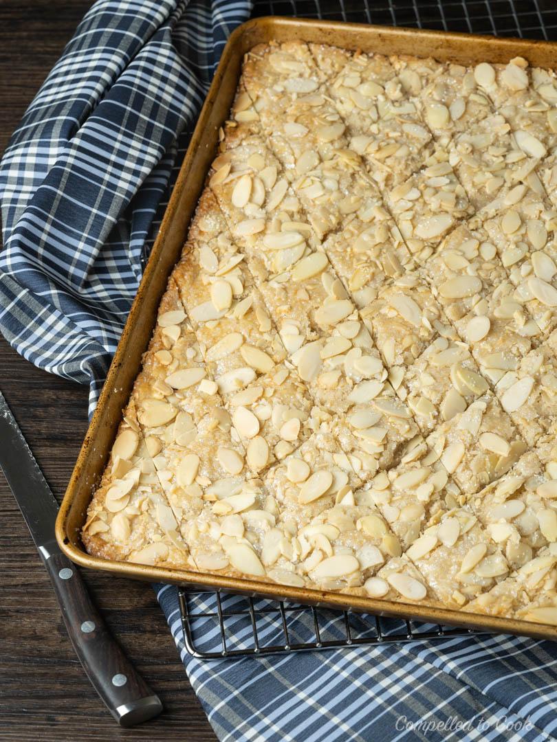 A sheet pan of freshly baked Jan Hagel Cookies resting on a wire rack.