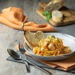 A shallow bowl filled with Red Pepper Spaghetti with Scallops and pieces of crusty bread.