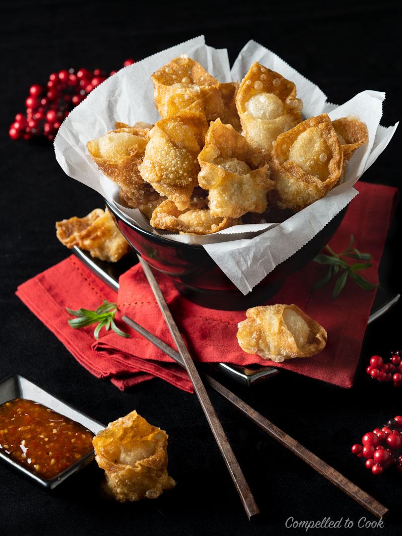 Crispy Wontons piled high in a brown bowl resting on a red napkin with a dark background.