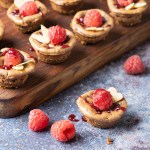Baked Keto Chocolate Raspberry Cheesecake Bites displayed on a wooden board with fresh raspberries and almonds on a blue background.