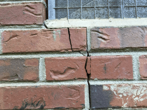 cracked exterior brick under window