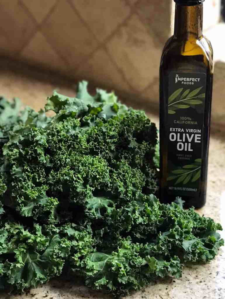 Up close shot of curly kale leaves and a bottle of olive oil