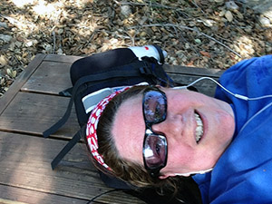 Laurie lies on her back on a bench at the top of the hiking trail
