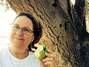 Close up by an oak tree of Laurie eating a green apple.