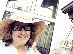 Laurie shows thumbs up in a straw hat and glasses in front of the windows of her house.
