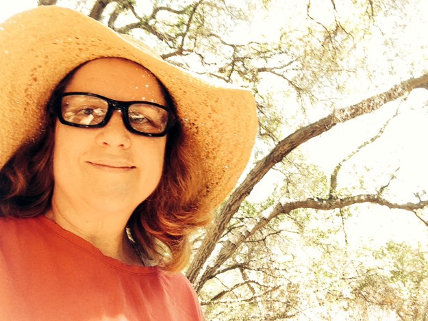 Laurie in her straw hat under a tree with a slight smile.