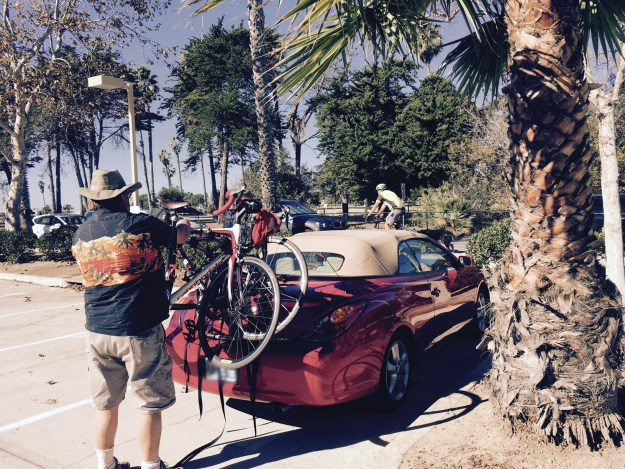 Mark fastens bikes to the back of a red convertible on a sunny day by palm trees
