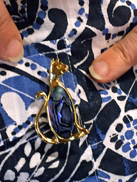 Close up of a gold cat pin with blue shell in center