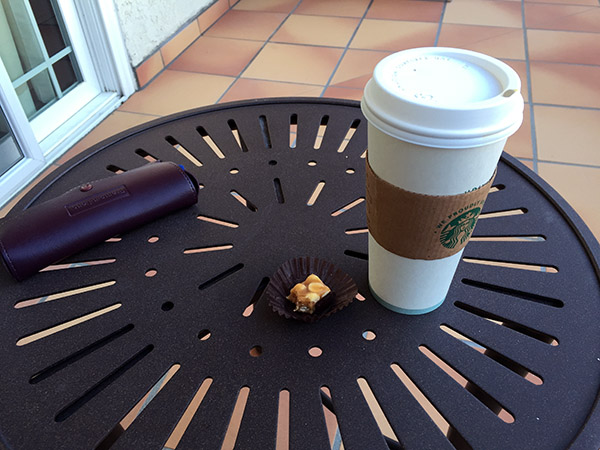 Coffee cup and half of a chocolate on a table
