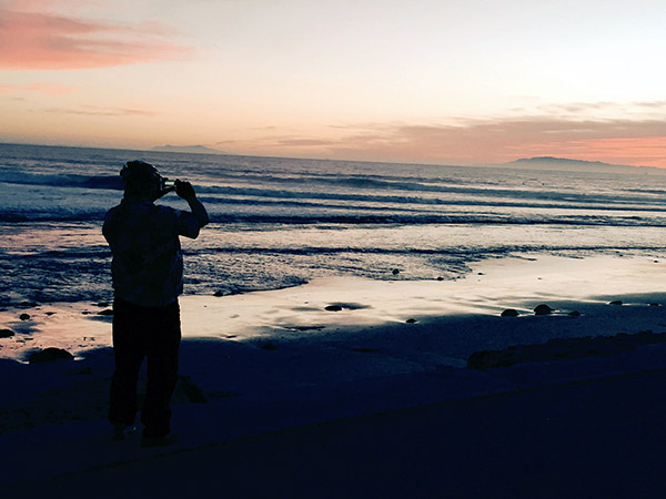 Mark in silhouette snapping a photo of sunset against the waves.