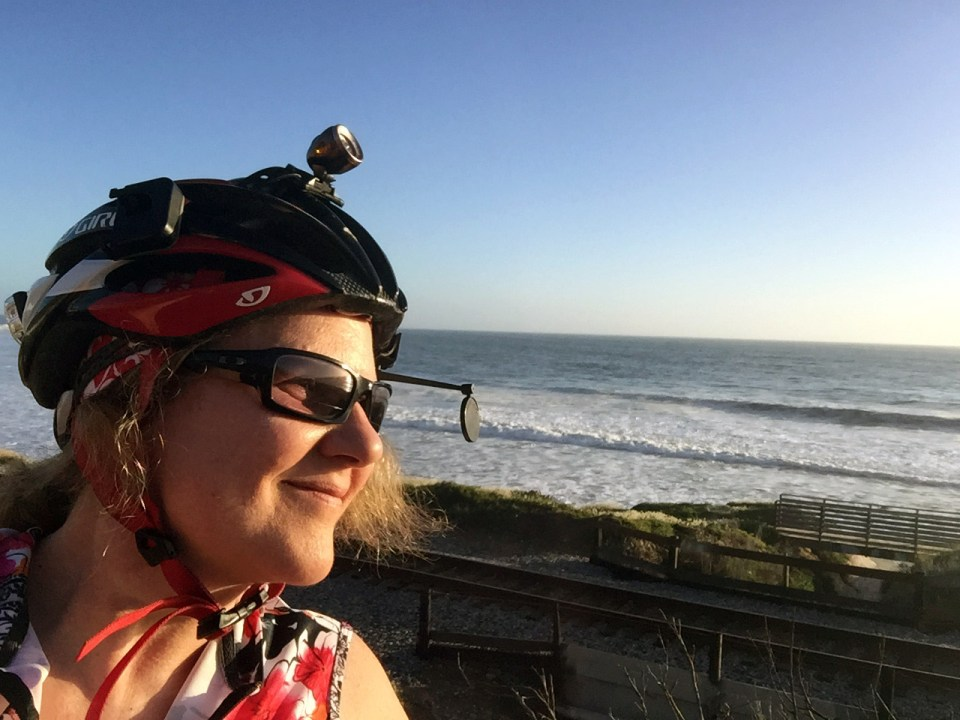 Laurie in bike gear looks out to sea with rolling waves on a sunny day.