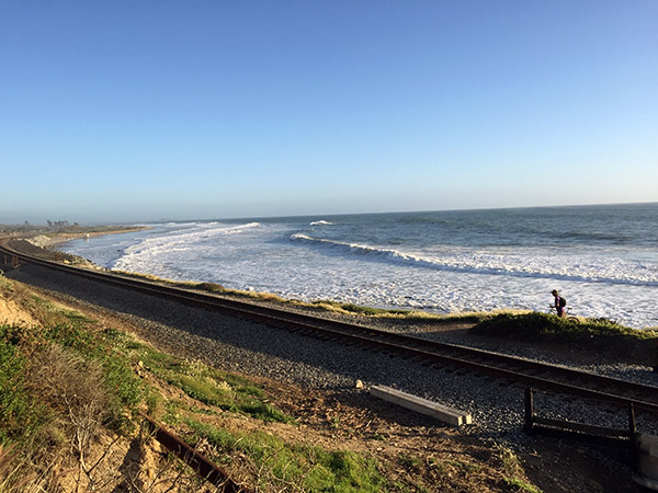 Sunny day, train tracks in foreground coastal waves beyond
