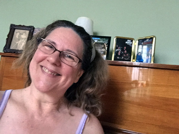 Laurie smiling by a piano