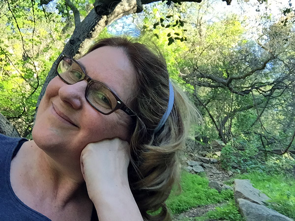 Laurie leans her cheek against her hand sitting under a tree down at the local park