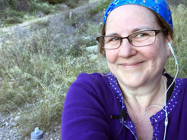 Laurie in blue scarf smiles against the wild grasses on the trail.