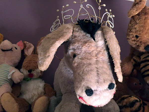 Stuffed Eeyore donkey toy wearing a tiara with the word BRAVE worked into it