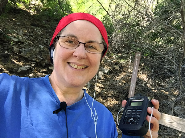 Laurie holding her recorder in the shade at the top of the trail