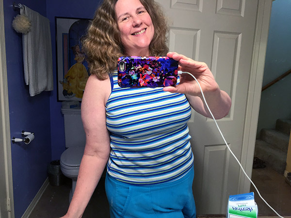 Laurie smiling as she takes a selfie in her mirror wearing blue shorts and a sleeveless striped tee.