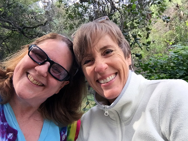 Laurie and Sandy in the grove of oak trees by the podcast rock