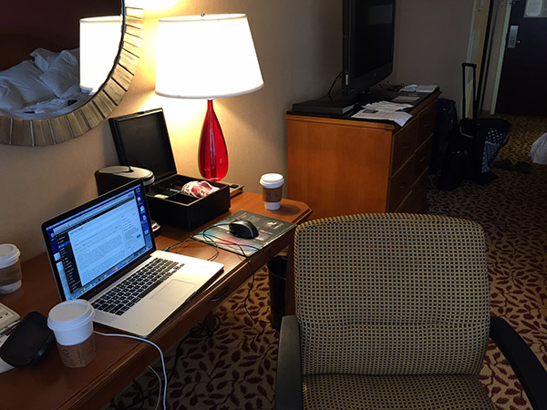 Hotel room desk with Laurie's computer and Starbucks coffee cup nearby