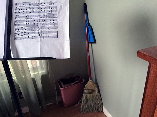 Broom in the corner next to the music stand holding music.