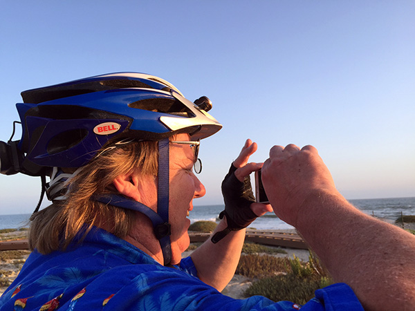 Mark in bike gear snapping photos at the beach