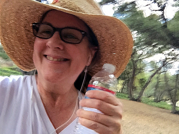 Laurie in sunhat holding a water bottle in the park