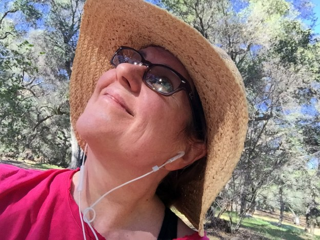 Laurie looking up wearing a straw hat and a peaceful look
