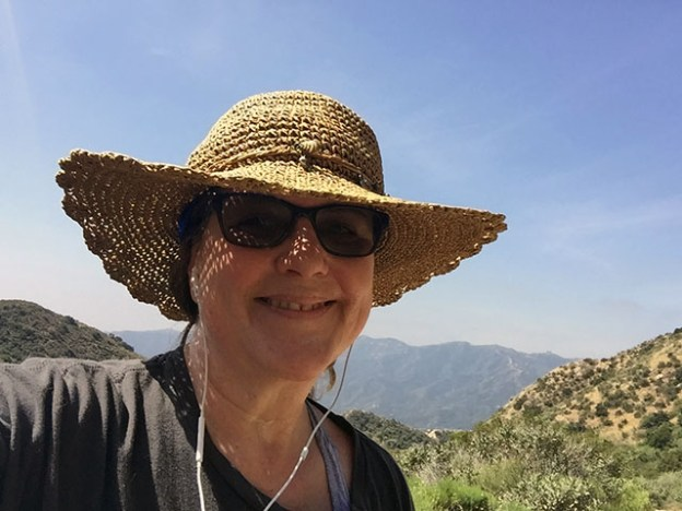 Laurie in her straw hat and sunglasses grins along the trail