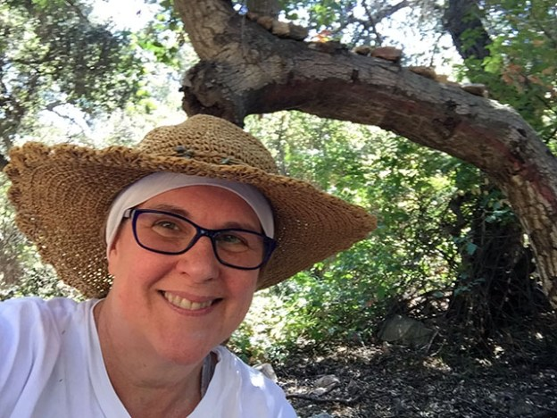 Laurie wearing a white shirt and sunhat smiles under a tree