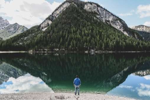 Man standing nearby sea in front of reflection of green mountain photo
