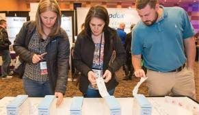 Attendees investigate the RxSafe PakMyMeds solution, one of many exhibitors.