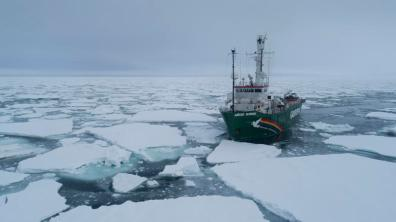 Aerial view of Greenpeace ship the Arctic Sunrise at the ice edge bringing scientists to take sea ice core samples, measure snow and ice thickness, and water column properties below the ice at the Arctic ice edge in Fram Strait, between Svalbard and Greenland. A group of US scientists is collecting data at the Arctic sea ice edge in May 2019 during the time of spring algae blooms to study the interactions between melting sea ice and the local ecosystem.