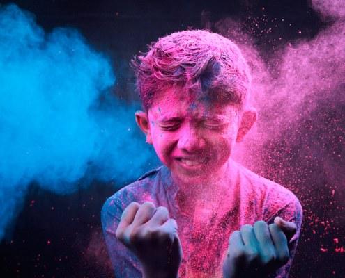 Niño cubierto de polvo colorado después de la Holi Fest