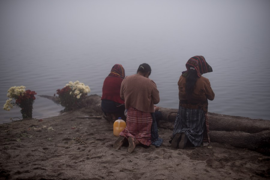 A group of women pray at the shores of lake Chicabal as the lake is covered in mist. Photo: Santiago Billy/Comvite