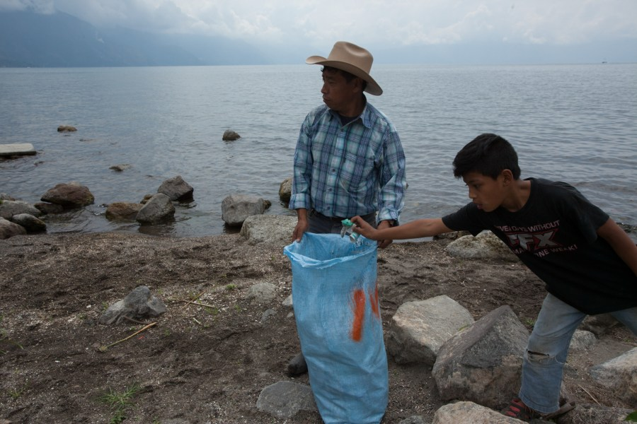 A local fisherman fills a sack from trash found on the shores of Lake Atitlan, in San Pedro La Laguna, Sololá, Guatemala.