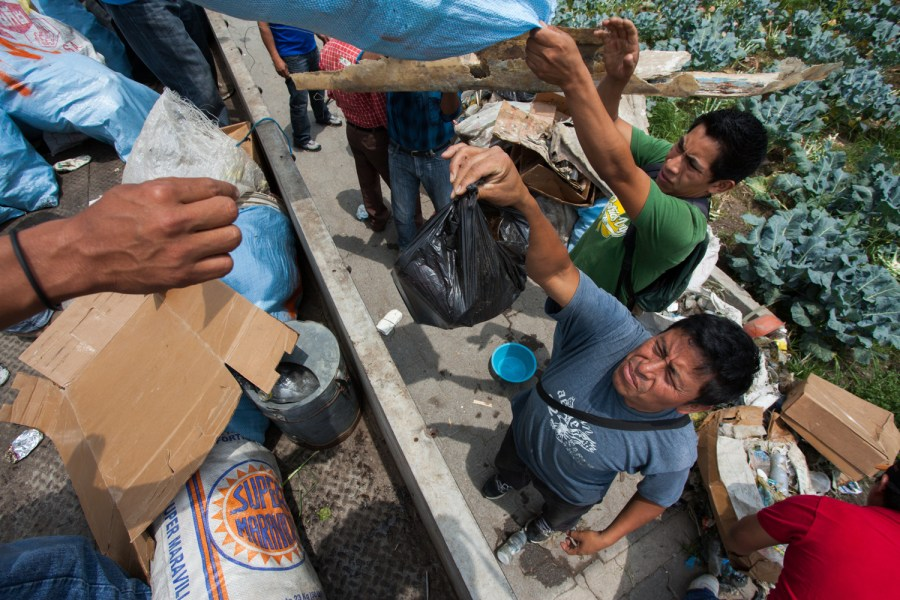 A group of fishermen help gather the trash onto a van for its disposal in San Pedro La Laguna, Sololá, Guatemala.