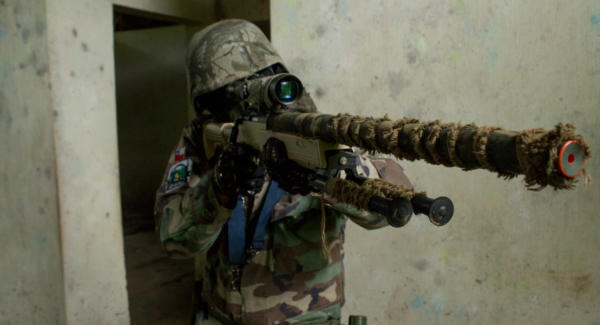A sniper aims at an opponent during an airsoft match in Guatemala. Photo: José A. Hernández Moll/Comvite