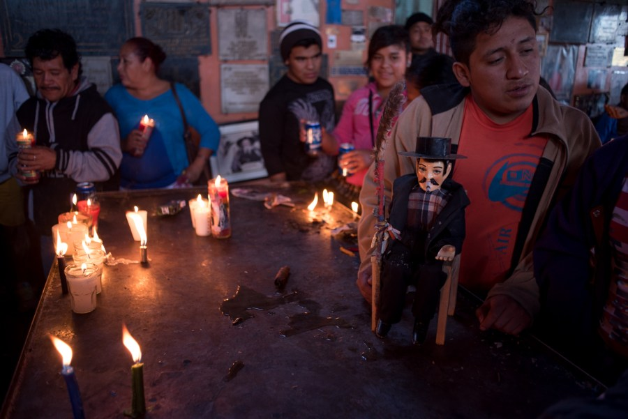 Followers of San Simón light candles as offerings to the devious deity. Photo: Santiago Billy/Comvite