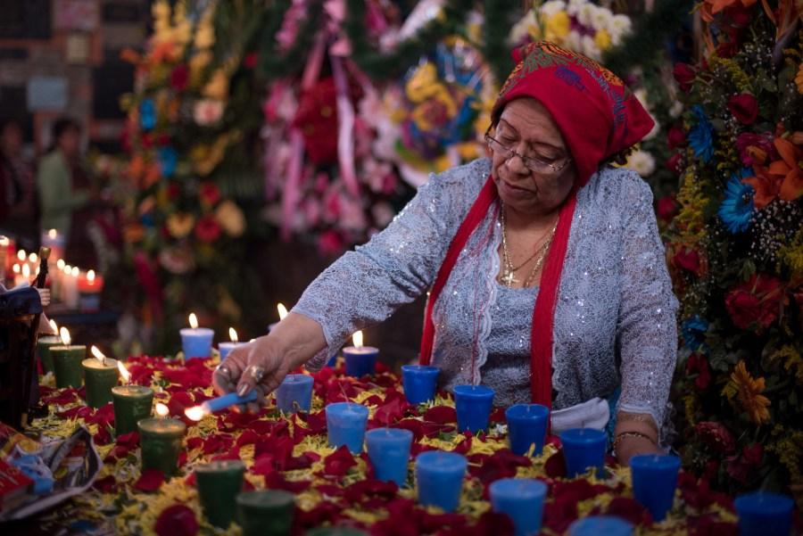 A woman lights candles in honor of San Simón. Photo: Santiago Billy/Comvite